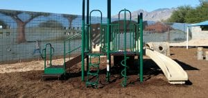 green playground with tan slide